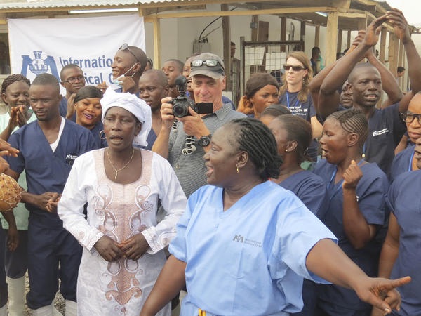 Adama Sankoh, 40 (center), who contracted Ebola after her son died from the disease late last month, stands with health officials the moment after she was discharge from Mateneh Ebola treatment center outskirt of Freetown, Sierra Leone.