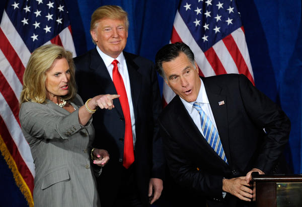 Mitt Romney peers over the podium at guests being pointed out by his wife, Ann, during an event at which Donald Trump endorsed Romney in 2012.