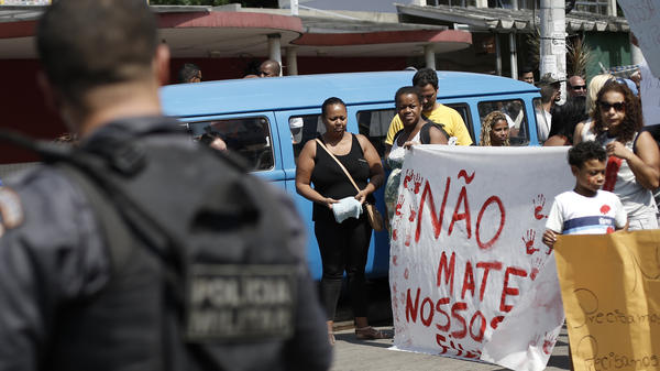 "Protesters hold a sign Saturday that reads, in Portuguese, ""Don't kill our children,"" in a march against police and gang conflicts that have left residents of the Complexo de Alemao favela in the crossfire."