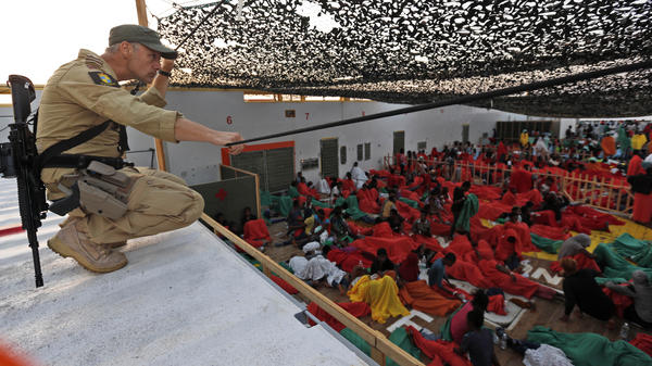 A Norwegian police officer on the bridge of the Siem Pilot ship watches over migrants rescued in the Mediterranean Sea on their way to the Italian port of Cagliari on Sept. 2. Hundreds of migrants were rescued a day earlier.
