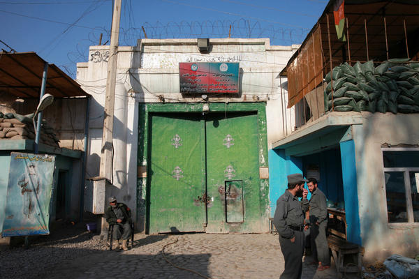 Men guard the gate of a women's prison in Afghanistan.