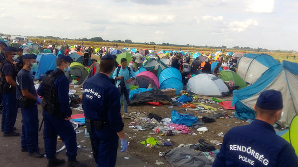 Hungarian police guard hundreds of migrants and refugees sleeping in a cornfield near an overcrowded detention center on the Hungary-Serbia border.