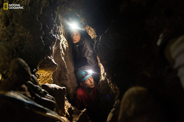 Anthropologist Lee Berger's daughter, Megan (top), and Rick Hunter, a member of the underground exploration team, navigate the narrow chutes leading to the Dinaledi Chamber of the Rising Star cave in South Africa. That's where fossilized bones belonging to <em>H. naledi,</em> a new species related to humans, were discovered.