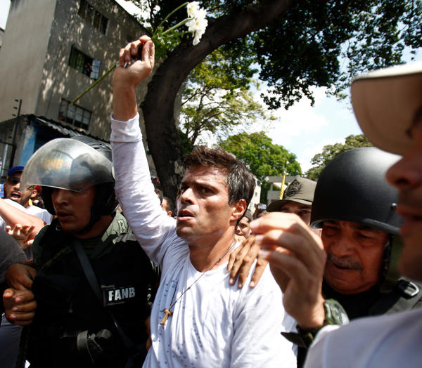 Opposition leader Leopoldo López is flanked by Bolivarian National Guards after surrendering in 2014.