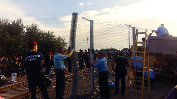Hungarian police unfurl chain-link fencing across one of the last remaining openings in a barrier that extends 110 miles across the Hungary-Serbia border.