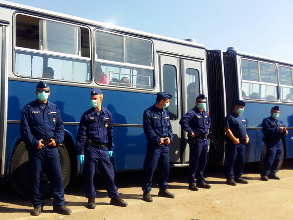 Hungarian police stand guard in front of buses taking migrants and refugees to the Austrian border.
