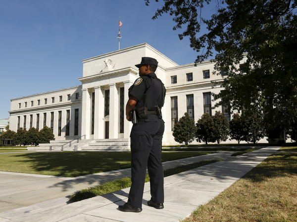 A police officer keeps watch outside the Federal Reserve headquarters in Washington, D.C., where policymakers weighed whether to boost interest rates.