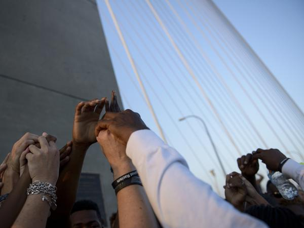 People interlock hands on the Arthur Ravenel Jr. Bridge in Charleston, S.C., a few days after nine black churchgoers were killed by a white shooter in June. A new PBS NewsHour/Marist poll finds attitudes about opportunities in the U.S. for blacks and whites contrast along racial lines. The poll will be discussed during PBS' <em>America After Charleston </em>broadcast Monday night.