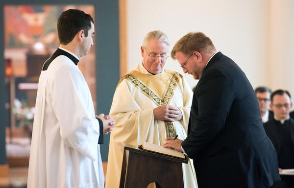 The Rev. Phillip Brown (center) watches as Tom Lawrence (right), a first-year pre-theologian at Theological College, signs the Book of Inscription during the school's opening Mass in August.