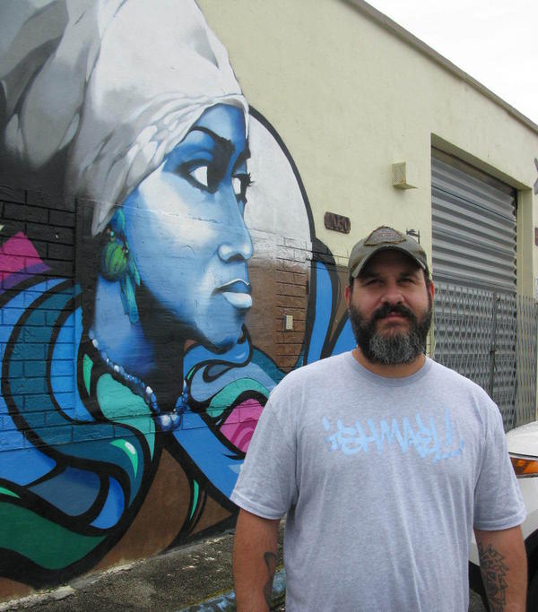 The graffiti artist, Trek6, stands with his symbolic mural.