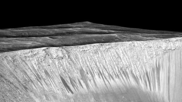 Streaks a few hundred feet in length appear on the walls of Garni crater on Mars. Scientists suspect they are formed by the flow of briny, liquid water on Mars.