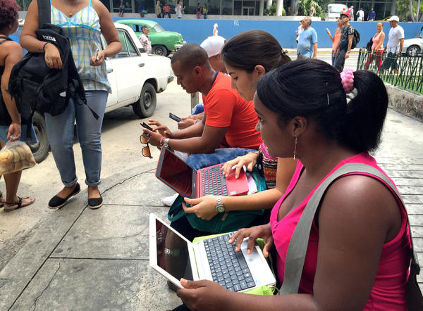 People huddle in front of the Habana Libre hotel in Havana, trying to get on the Internet.