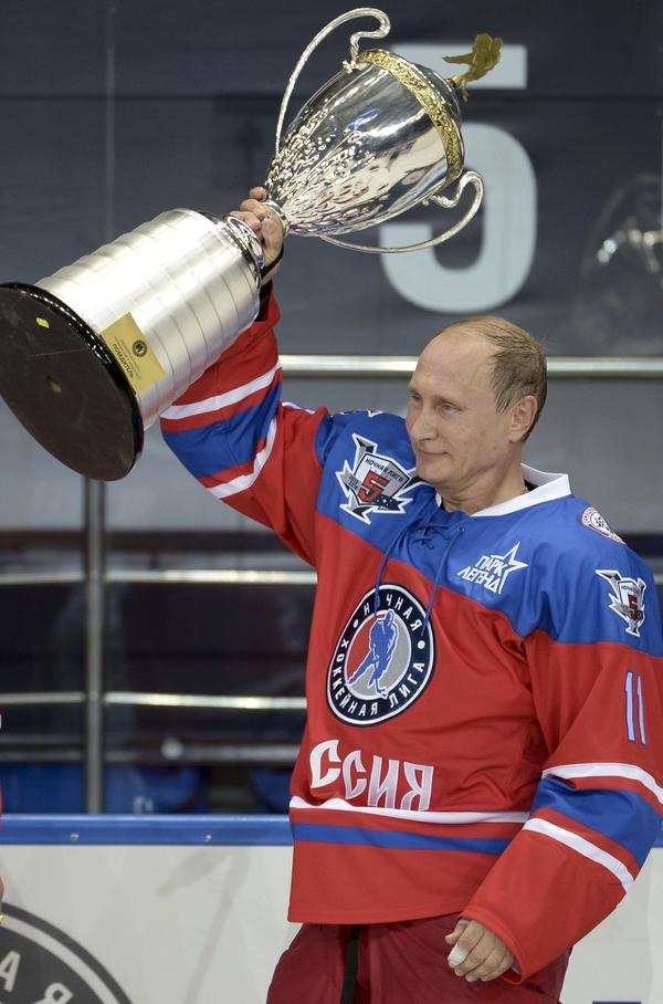 Putin holds a trophy at his birthday hockey match, during which he scored seven goals.
