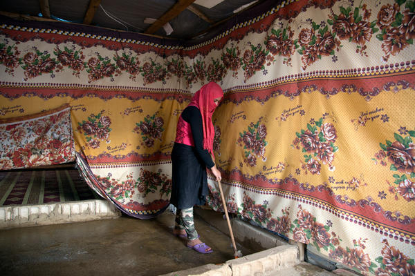 """After lunch, Fatmeh cleans the tent where she lives with her family. Her new life, she says, is """"work, work, work."""""""