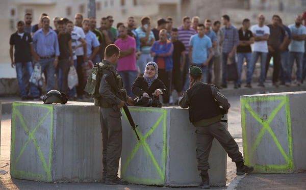 Israeli police check Palestinian IDs at a checkpoint in an Arab neighborhood of Jerusalem on Sunday. Palestinian assailants have carried out a series of stabbings and the Israelis have ramped up security measures in the city. Eight Israelis and more than 30 Palestinians have been killed in recent violence.