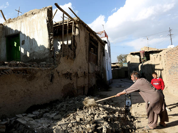 An Afghan man clears rubble from a damaged house after the earthquake shook the region. The epicenter was approximately 150 miles from Kabul, Afghanistan.