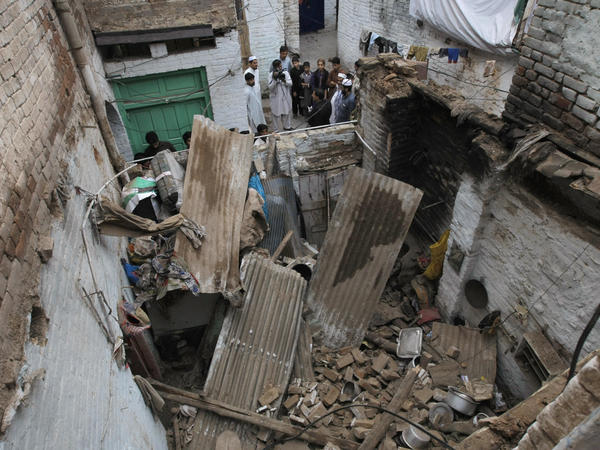 People stand outside a house damaged from an earthquake in Peshawar, Pakistan, after a powerful earthquake in northern Afghanistan rocked cities across South Asia.