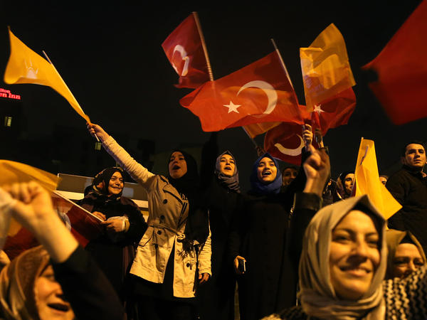 Supporters of Turkey's President Recep Tayyip Erdogan and the Justice and Development Party (AKP), wave their party and national flags as they celebrate outside the AKP headquarters, in Istanbul.
