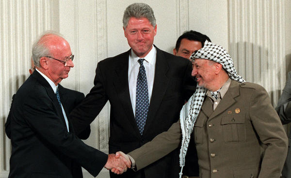 Israeli Prime Minister Yitzhak Rabin (left), and Palestinian leader leader Yasser Arafat reach an interim agreement as President Clinton looks on at the White house on Sept. 28, 1995. Rabin was killed by an extremist Jew five weeks later.