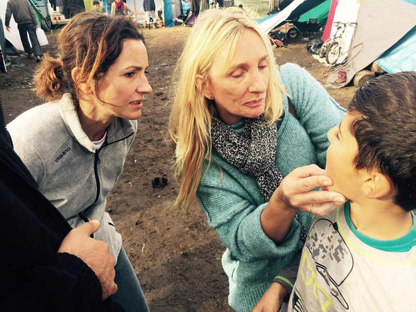 Teachers Virginie Tiberghien (left) and Nathalie Janssens check an Iraqi boy's mouth because he has a toothache. The camp has volunteer doctors to provide treatment.