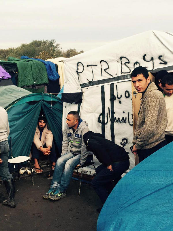 Young men hang out around their tent neighborhood. Many tents have blankets on the floor, and people take off their shoes before going inside.