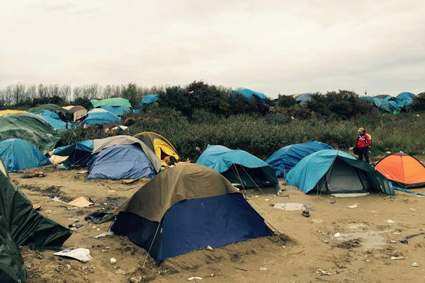 "Tents dot the scrub brush in the dunes at ""The Jungle,"" a camp in Calais, France, that houses about 6,000 migrants."