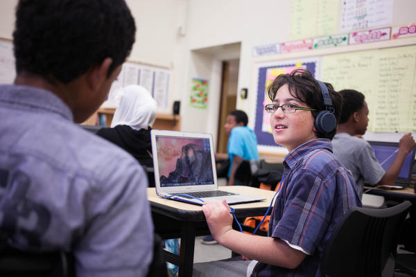 Adam Livneh speaks to a classmate in his sixth-grade Spanish class. All of the students use the language learning app Duolingo on their laptops. Since students enter the school with varying language abilities, they are able to start the program at a level tailored to them.