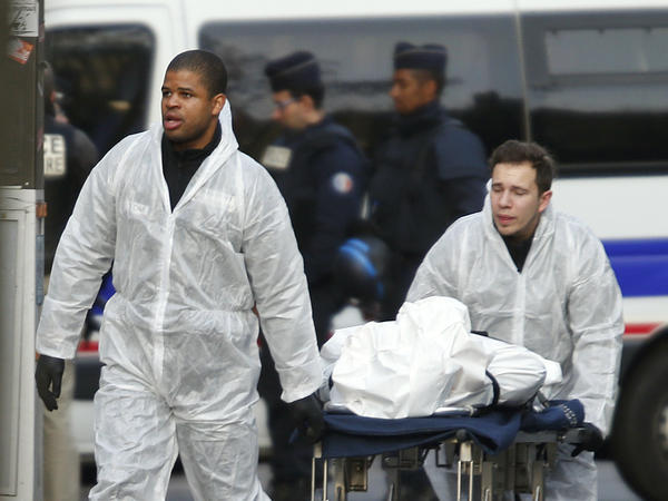 A victim is wheeled out of the Bataclan concert hall Saturday morning after a series of deadly attacks in Paris.