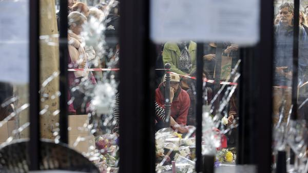Bullet holes are seen in the windows of the cafe 'Bonne Biere' as people stand outside to mourn the victims in Paris, on Sunday, following a series of coordinated terrorist attacks that left 129 people dead and many more wounded.
