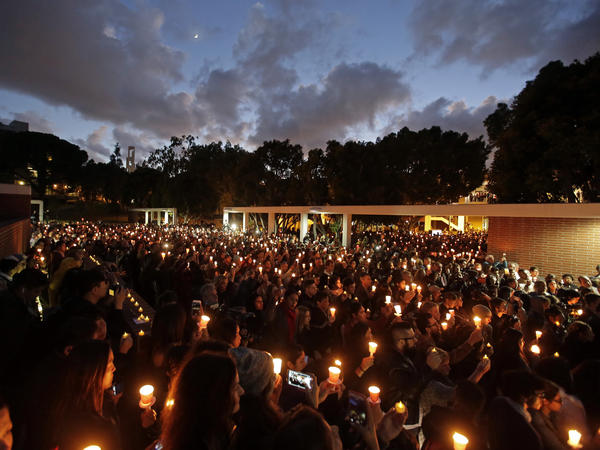 Well-wishers hold up candles during Nohemi Gonzalez's memorial service on Sunday.