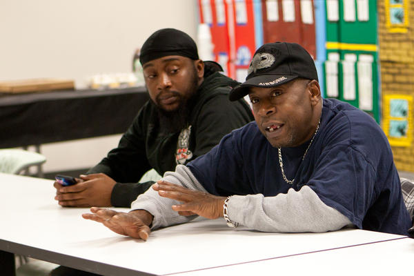 Harrelle Felipa (right) speaks during the Responsible Fatherhood meeting at the Center for Urban Families in Baltimore. His child support debt has accrued to $20,000 after he quit a job to be a stay-at-home dad.