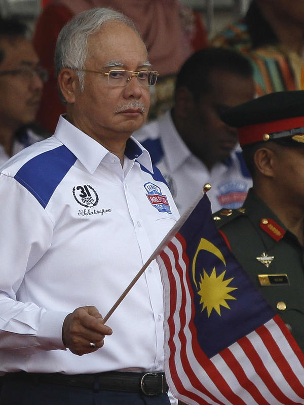 Malaysian Prime Minister Najib Razak waves the Malaysian flag during National Day celebrations on Aug. 31. He has faced widespread criticism and protests over allegations that huge sums disappeared from a government-owned investment fund.