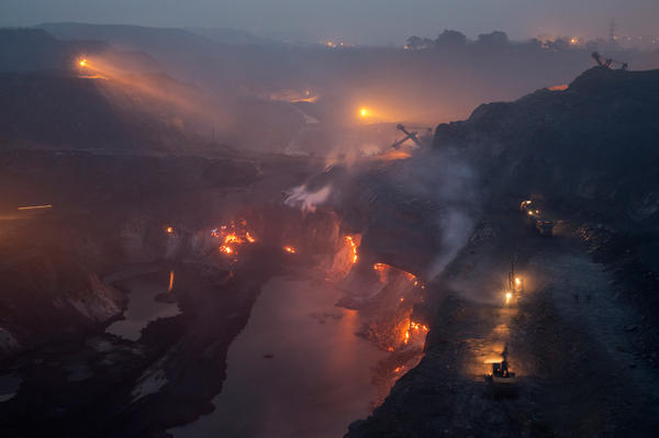 Coal fires burn early in the morning in January 2014 at a privately owned coal mine in India's Jharkand state, making the air dense with noxious smoke and dust. Forty percent of India's mineral wealth lies in Jharkhand.