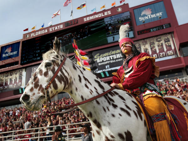 The FSU student portraying Osceola stands in front of a crowd at the FSU homecoming game.
