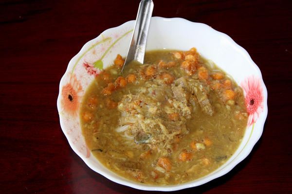 A bowl of mohinga, a flavorful fish stew with vegetables and rice vermicelli.