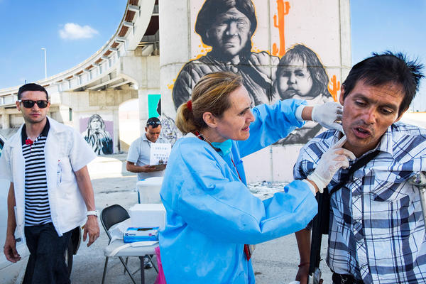 Dr. Patricia Gonzalez examines a patient's neck at a first-aid clinic that she started in 2014 in the Tijuana River Canal, where hundreds of drug users live. Some of them inject in the neck; wounds can result.