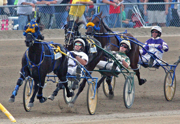 Yes, the Little Brown Jug harness race lives on. The horse in the lead here, Vegas Vacation, driven by Brian Sears, holds on to win the 2013 race in Delaware, Ohio.