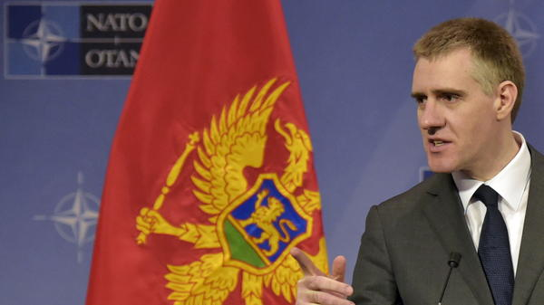 Standing beside his country's flag, Foreign Minister Igor Luksic of Montenegro attends a news conference after Wednesday's meeting at NATO headquarters in Brussels.