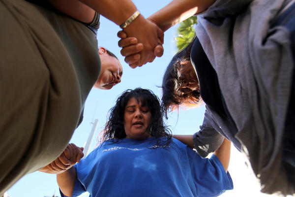 Marie Cabrera, Sonya Gonzalez and Christine Duran, all of San Bernardino, pray after the shooting.