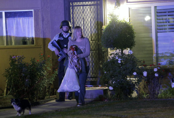 A police officer escorts a woman from a home in Redlands, Calif., following the shooting in San Bernardino.