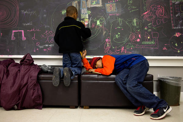 Nikia Cliff II, 6, colors on the chalkboard inside the Major Chords for Minors office before his piano lesson, while his older brother Khalil Cliff, 10, takes a nap before his drum lesson.