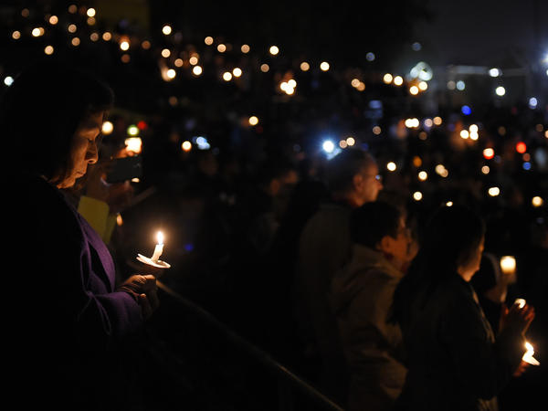 People hold candles during a vigil for shooting victims in San Bernardino, California.