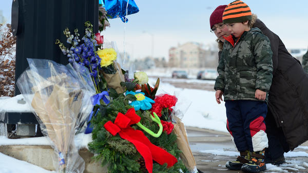 Nasya Fair and her son Korbyn, 4, look at a growing memorial for the Colorado Springs, Colo., shooting victims. Colorado and California are the latest states at the center of the gun control debate.