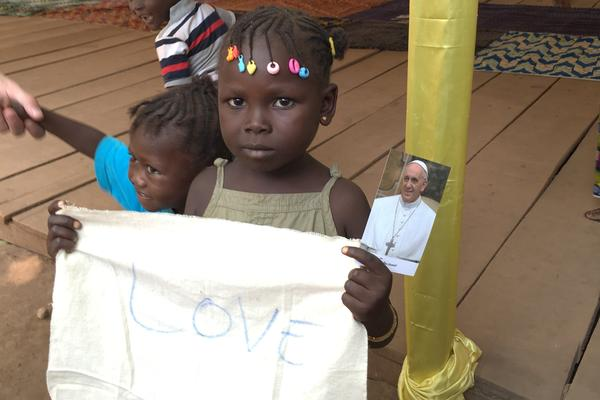 """A girl holds up a sign reading """"Love,"""" at the Saint Sauveur displaced persons camp in Central African Republic."""