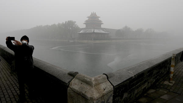"""A tourist takes a selfie near the Turret of the Forbidden City in Beijing. The city issued a """"red alert"""" Monday over dangerous levels of air pollution."""