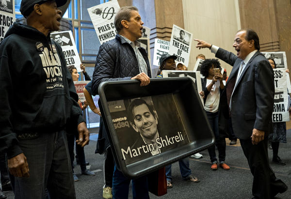 "AIDS activists and others carry an image of Turing Pharmaceuticals CEO Martin Shkreli and signs decrying ""Pharma greed"" during a protest Oct. 1. Shkreli's company bought an antiparasitic drug and increased the price 5,000 percent."
