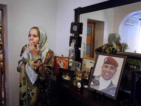 Latifa Ibn Ziaten prayed during an October 2012 tribute ceremony at her family home honoring the memory of her son, Imad, shown in a framed picture.