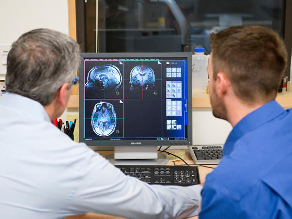 Jeffrey Iliff (right) and Bill Rooney, brain scientists at Oregon Health & Science University, look over an MRI. The school has an especially sensitive MRI unit that should be able to detect precisely when during sleep the brain is being cleansed of toxins.
