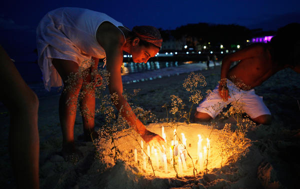 Revelers light candles on Copacabana beach during New Year's Eve celebrations in Rio de Janeiro.