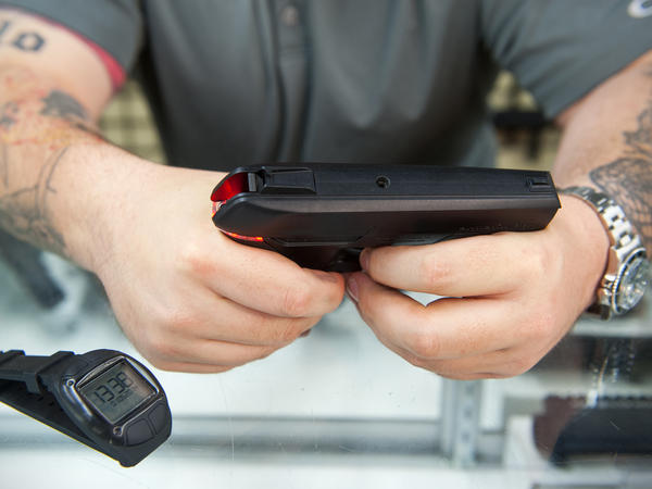 Andy Raymond demonstrates the Armatix iP1, a .22-caliber smart gun that has a safety interlock, at Engage Armaments in Rockville, Md., last year.